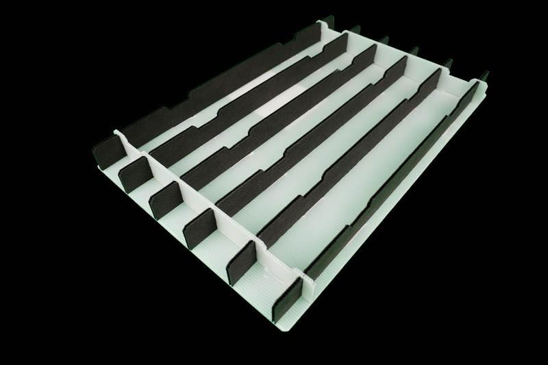 Ein weißes Kunststoff Gefache mit schwarzen Einsätzen dient als Mehrwegverpackung - Tillmann Verpackungen Schmalkalden GmbH