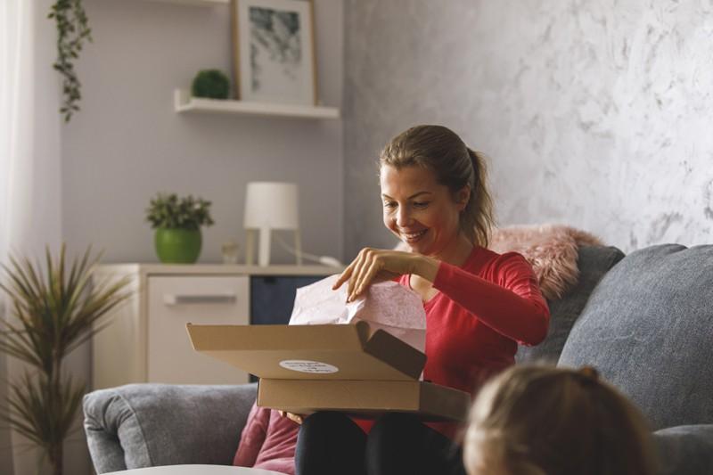 Frau sitzt auf einer Couch und öffnet ein Paket aus dem Online Versandhandel